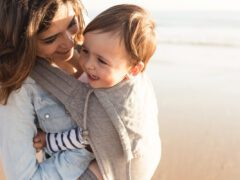 A mom wears her baby in a baby carrier at the beach