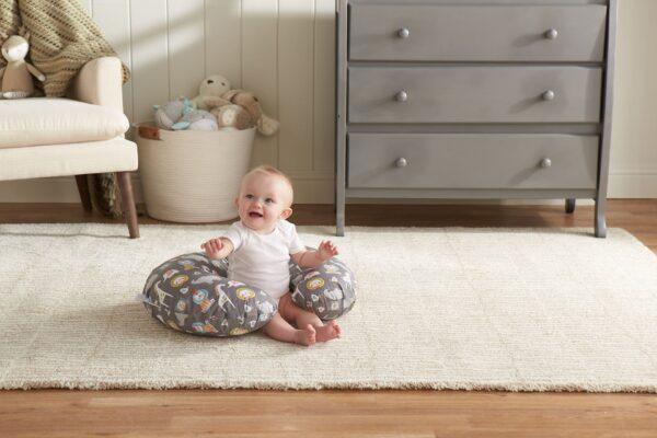 Baby sitting on the floor in Boppy nursing pillow