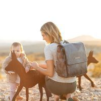 Mom carries a Petunia Pickle Bottom Boxy diaper bag backpack